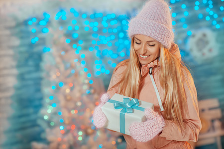 Merry Christmas and Happy New Year! Portrait of happy cheerful woman in mantis holding mantens holding present box on Christmas background. Holiday Card with greetings and snowflakes.