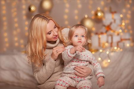 Feliz Navidad y Felices Fiestas! Niño pequeño con mamá sentada en sala decorada con regalos y luces y disfrutando. Hija y madre pasando vacaciones juntos. Conceptos de Año Nuevo Familiar