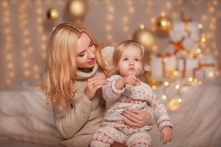 Merry Christmas and Happy holidays! Small kid with mom sitting in decorated room with gifts and lights and enjoying. Daughter and mother spending holiday together. Family New Year concepts Stock Photo