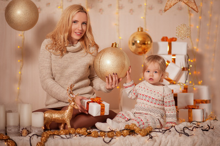 Merry Christmas and Happy holidays! Small kid with mom sitting in decorated room with gifts and lights and enjoying. Daughter and mother spending holiday together. Family New Year concepts Foto de archivo