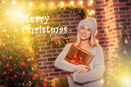 Merry Christmas and Happy New Year! Portrait of happy cheerful beautiful woman in knitted hat sweater holding holiday present box on Christmas background. Holiday Card with greetings and snowflakes. Stock Photo