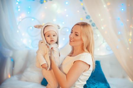 ¡Feliz Navidad! hermosa joven madre con niño divertirse en un dormitorio decorado en Navidad. Navidad, año nuevo, familia, concepto de vacaciones.