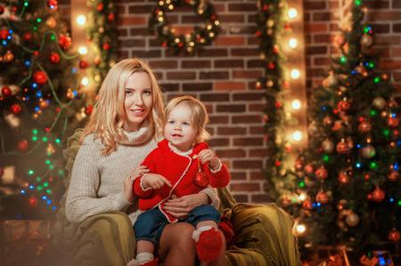 Feliz Navidad y Felices Fiestas! Madre alegre y su hija linda sonriendo y divirtiéndose en el fondo de Navidad. Padres y niños pequeños divirtiéndose cerca de árbol de Navidad en el interior. Foto de archivo