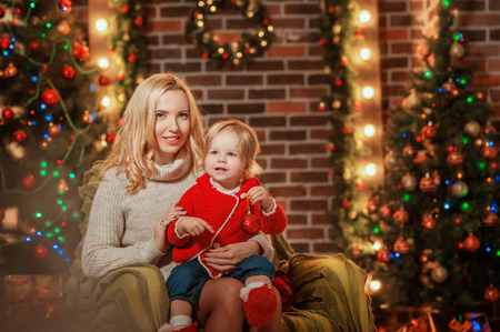 Merry Christmas and Happy Holidays! Cheerful mom and her cute daughter smiling and having fun on christmas background. Parent and little child having fun near Christmas tree indoors. Stock Photo