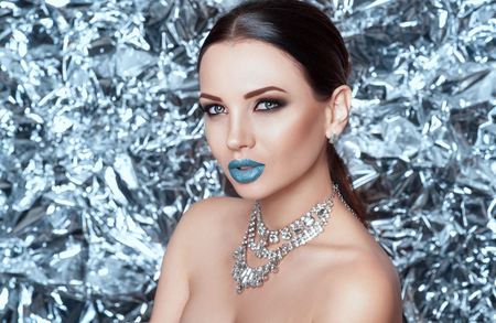Belleza de invierno Chica hermosa modelo de moda con labios de nieve azul. Maquillaje de vacaciones en fondo brillante de brillo y joyas brillantes. Reina de invierno.