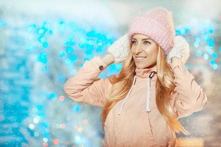 ¡Feliz Navidad! Hermosa joven rubia con sombrero y mitones sonriendo fuera sobre fondo de Navidad con luces. Concepto de vacaciones, Navidad, año nuevo, invierno, personas.