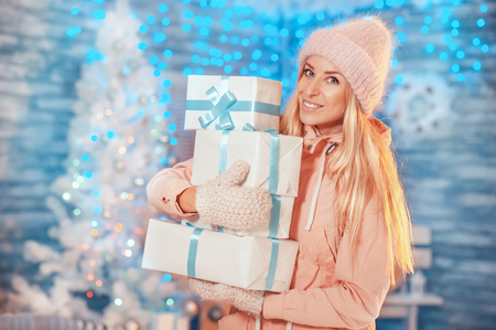 Merry Christmas! Attractive young woman in knitted hat holding gift boxes and smiling while standing outdoor on christmas light background and christmas tree. Stock Photo
