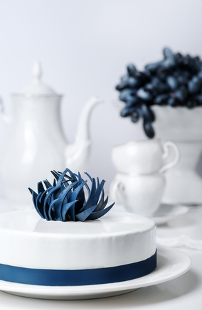 Holiday white mousse cake decorated with blue creative flower with tea set and grape on stand cake on background. Vertical Food Drink Concept. Wedding classic pastry in restaurant. Celebrating Sweet Stock Photo