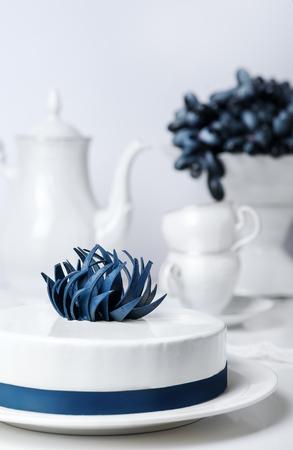 La torta blanca de la crema batida del día de fiesta adornada con la flor creativa azul con el juego de té y la uva en soporte se apelmaza en fondo. Concepto de bebida de comida vertical. Boda pasteles clásicos en el restaurante. Celebrando dulce
