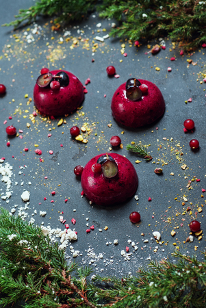 Trendy mousse cake with berry glaze decorated with fir tree Meringues Cranberry. Holiday sweet composition of dessert