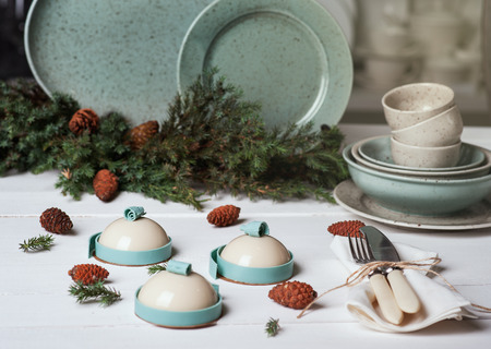 Trendy mousse cake with mirror glaze decorated fir tree, pine cone and plate with cups on background. Holiday decoration. Winter composition with mini cakes Foto de archivo