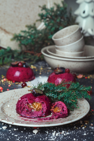 Delicious trendy mousse berry cake with honey filling on holiday table decorated with plate and cup set Fir tree Pine Cone. Home Pastry Rustic Dinner Holiday Winter concept. Cookery at cozy home Stock Photo