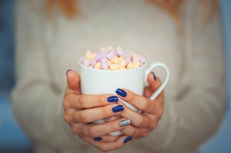 Ciérrese para arriba de manos de una mujer joven con una manicura que sostiene una taza de cacao caliente con la ventana cercana interior del melcocha o del café en el suéter.