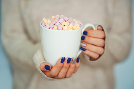 Close up of hands of a young woman with a manicure holding a cup of hot cocoa with marshmallow or coffee indoor near window on sweater.