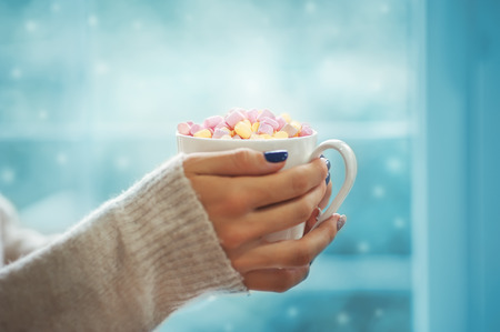 Close up of hands of young woman with manicure holding a cup of hot cocoa with marshmallow or coffee. Stock Photo