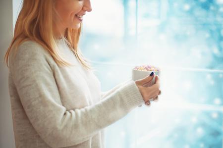 Ciérrese para arriba de mujer joven hermosa en el suéter que sostiene la taza de cacao o de café caliente con la melcocha mientras que se coloca cerca de la ventana interior y la mirada para nevar al aire libre.