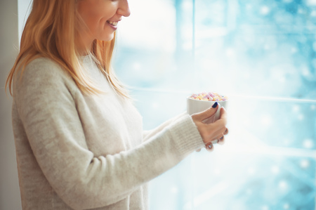 Close up of beautiful young woman in sweater holding cup of hot cocoa or coffee with marshmallow while standing near window indoor and looking to snow outdoor.