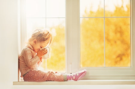 Little cute kid girl sitting by window holding a cup of hot drink cocoa enjoying autumn forest background. Season Beauty fashion Children concepts. Fall season