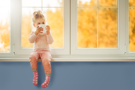 Little cute Kid Girl sitting by window holding cup of hot drink cocoa enjoying autumn forest background. Season Beauty fashion Children concepts. Fall season