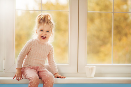 Ð¡ute little kid girl in pajama sitting by big window playing smiling enjoying home. Cacao cup standing on window. Autumn Season Interior Family Textile industry Holiday People concept