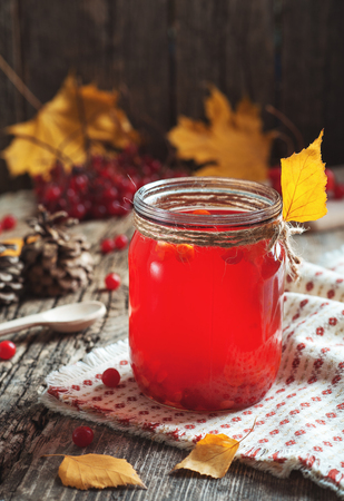 Close up hot Red Drink in glass with cranberry or viburnum berry on wooden table with autumn leaves at village. Food Drink Family Tradition Cooking cuisine concepts. Cozy evening at home holiday