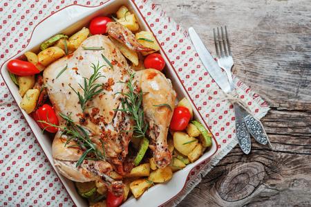 Pollo entero asado relleno de verduras, tomates patata pimienta y romero en el fondo de la mesa de madera de servilleta vintage con tenedor y cuchillo conjunto. Vista superior, espacio de copia, concepto de comida de vacaciones.