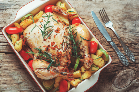 Roasted whole chicken stuffed with vegetables, tomatoes potato pepper and rosemary on vintage napkin wooden table background with fork and knife set. Top view, copy space, holiday food concept.