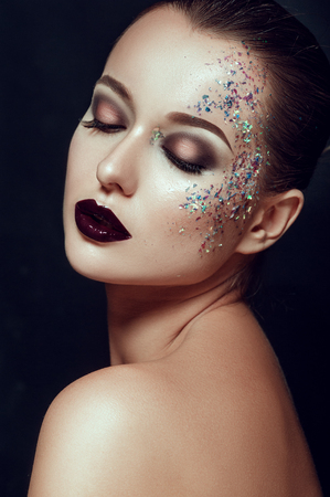 close-up beauty portrait of attractive sexual woman with fashion evening art make up with sparkles. People Beauty industry Lifestyle Skincare Woman concepts. Perfect skin Dark lipstick
