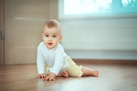 Adorable little baby sitting in a bedroom on the floor with a bottle of milk or water and laughing. Infant Childhood Kids People concepts. Cozy home with children Lifestyle