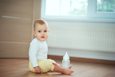 Adorable little baby sitting in a bedroom on the floor with a bottle of milk or water and laughing. Infant Childhood Kids People concepts. Cozy home with children Warm