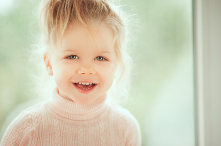 Close up portrait of adorable beautiful baby girl smiling and looking to cam. Childhood Kids People concepts. Caucasian Fashion Beauty