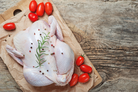 Raw chicken meat with rosemary pepper and tomatoes on wooden board ready for cook. Rustic background. Food Kitchen Cuisine Health concept. Diet meal