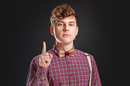 Fresh idea! Attention! Handsome young man in vintage shirt and curly hair holding. People Emotions Fashion Business