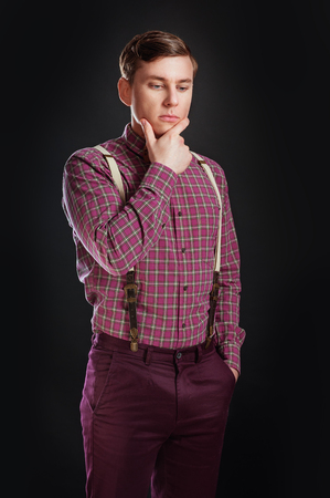 Portrait of thoughtful serious clever scientific man in vintage shirt tie with hairstyle keeping hand under chin while standing black background. Emotions People Education Business Fashion concept Stock Photo