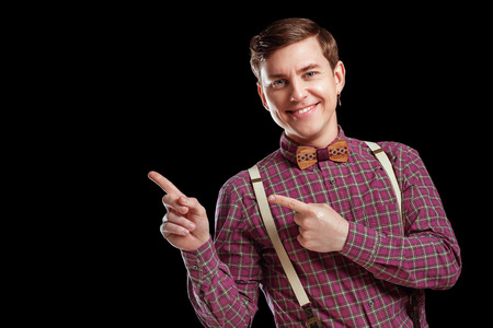 Look at this! Handsome young man in vintage shirt tie pointing copy space and smiling while standing against a black background. Education Emotios People Business concepts Stock Photo