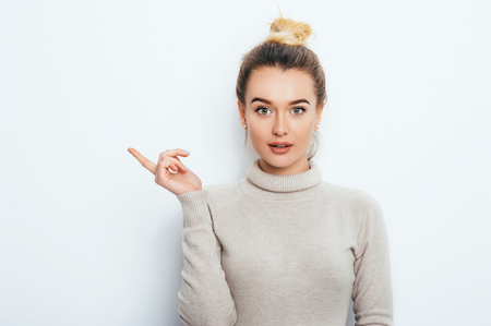 Look There! Surprised Attractive young female lady wearing sweater with hair bun showing emotions on white wall. Shocked woman points with forefinger at copy space on white background. Amazement Stock Photo