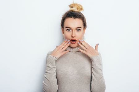 Positive shocked female with attractive look and lips wearing in sweater posing against white wall. Happy woman with bun touching face showing emotions. People Lifestyle Beauty Fashion concepts Stock Photo