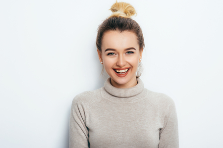 Horizontal portrait of a cheerful woman with an appealing smile, having a hair bun wearing a sweater.