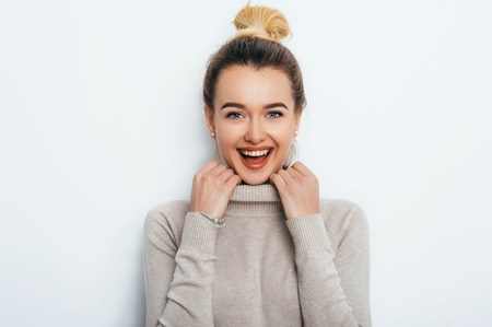 Smiling positive female with attractive look and lips wearing in sweater posing against white wall. Happy woman with hair bun showing positive emotions. People Lifestyle Beauty Fashion concepts Stock Photo
