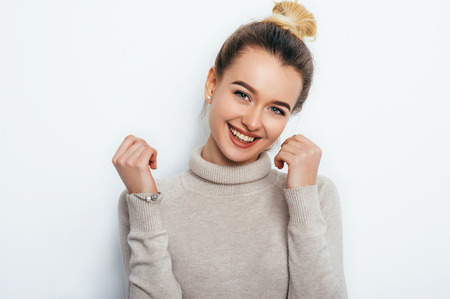 Cheerful young good looking woman with adorable smile hair bun posing on white isolated background. smiling. People Emotions Beauty