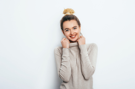 Portrait of a cheerful looking woman with an appealing smile, having a hair bun wearing a sweater. Beautiful female showing her pleasant emotions. People Beauty Fashion