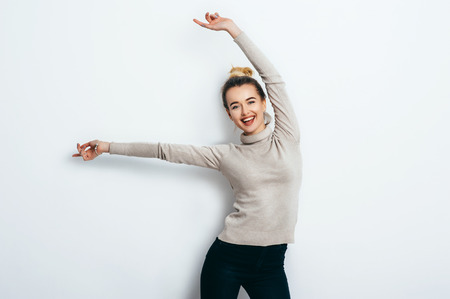 Young beautiful cheerful woman with bun wearing jeans and sweater dancing and posing over white wall. Good mood. Hands up! People Emotions Beauty Fashion Lifestyle concepts