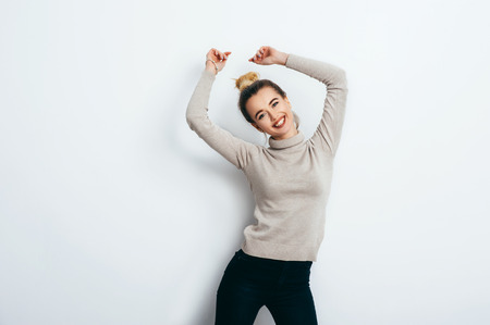 Young beautiful cheerful woman with bun wearing jeans and sweater dancing and posing over white wall. Good mood. People Emotions Beauty Fashion Lifestyle concepts Stock Photo