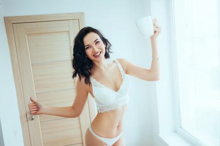 Starting day with fresh coffee. be energy at morning. beautiful woman in lingerie and curly hair holding white cup while dancing at home near big window.