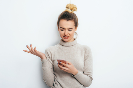 Horizontal portrait of displeased woman has indignant expression while holding smartphone, frowns eyebrows, can`t understand something, isolated on white background. Discontent emotion on face girl