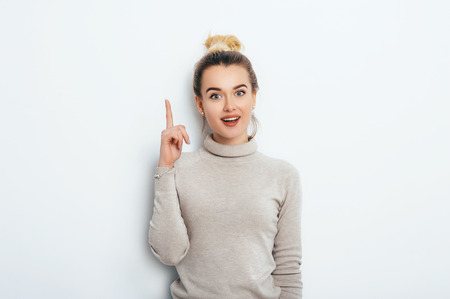 Adorable beautiful young woman with hair bun in sweater gets a good idea in mind raised forefinger on isolated white background. Lifestyle fashion Beauty