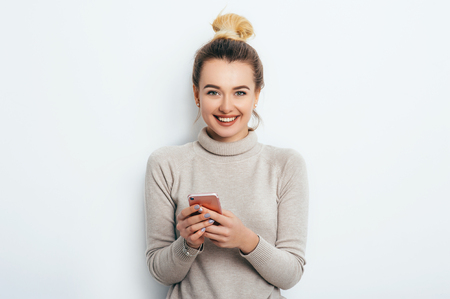 Happy cheerful happy woman with bun nude makeup wearing in sweater standing indoors with her smartphone chatting with friends or boyfriend. Lifestyle Fashion Beauty business concept