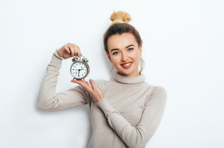 Portrait of beautiful young cheerful blonde woman with bun in sweater holding alarm clock and show emotions while standing over solated white background. Lifestyle Fashion Beauty Business Student Stock Photo