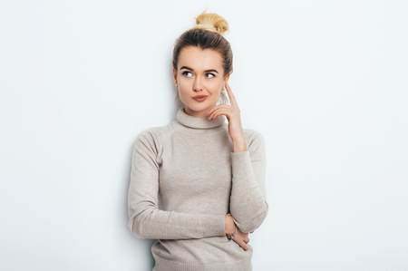 Portrait of attractive thoughtful young woman wearing her blonde hair in knot holding forefinger up looking away with sly smile. Pretty girl having thoughtful dreamy look posing at studio wall Stock Photo