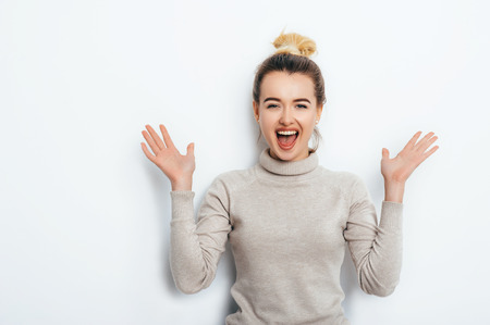 Horizontal portrait of a cheerful woman with a delighted emotion, having a hair bun wearing a sweater isolated over a white background. Beautiful female showing her pleasant emotions. People Beauty Fashion